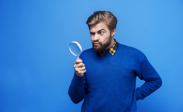 Surprised man looking through a magnifying glass